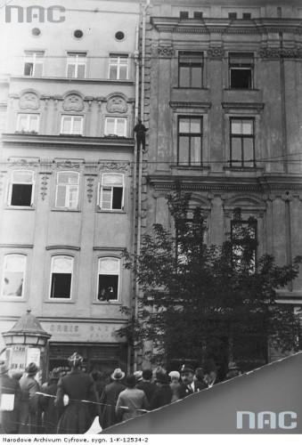 Feliks Nazarewicz wspina się po elewacji Pałacu Spiskiego na Rynku Głównym.